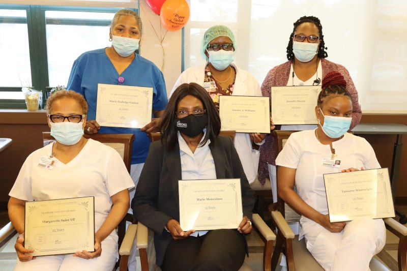 Group of employees holding certificates