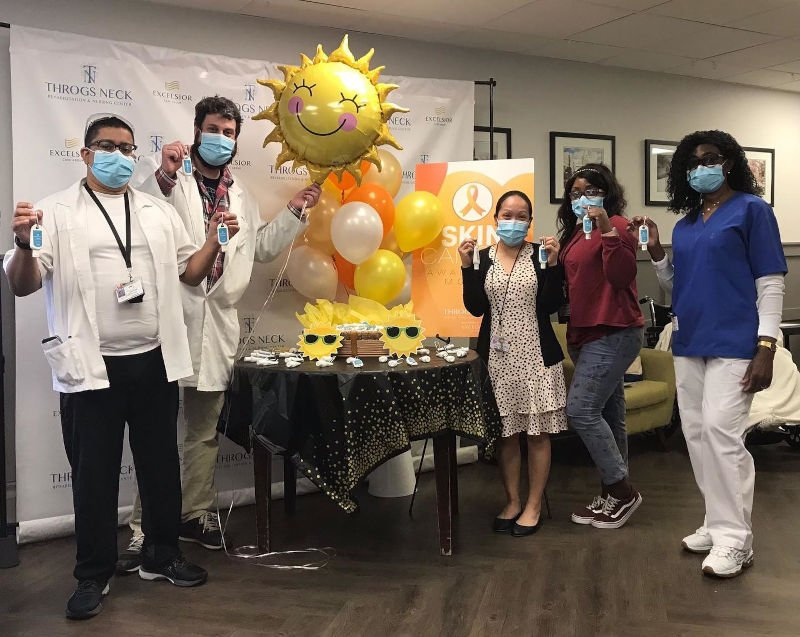 Group of employees standing around a table with a sunshine balloon above it